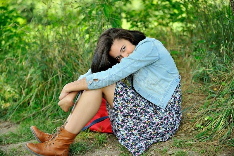 Giovane donna Biracial che si siede nell'erba fotografia stock libera da diritti