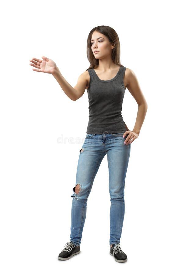 Giovane donna in bordo grigio e blue jeans che stanno, una mano sull'anca e l'altro tenuto in mano fuori come se swiping su invis immagini stock libere da diritti