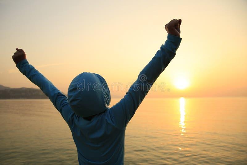 giovane donna a braccia aperte sulla spiaggia di alba fotografia stock libera da diritti