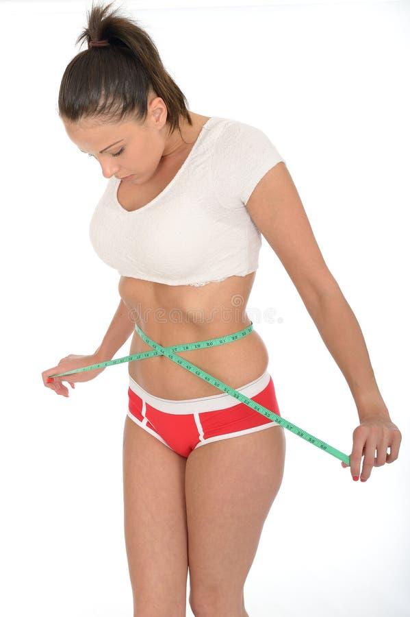 Giovane donna in buona salute che controlla la sua perdita di peso con una misura di nastro fotografia stock libera da diritti