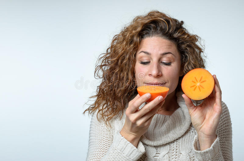 Giovane donna in buona salute che gode di un cachi immagini stock