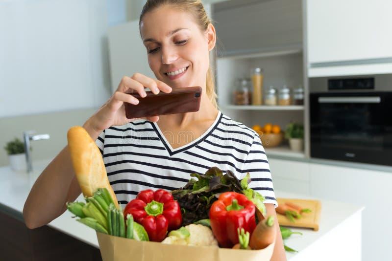 Giovane donna in buona salute che prende una foto con il suo telefono mentre tenendo le verdure nella borsa di drogheria nella cu fotografia stock libera da diritti