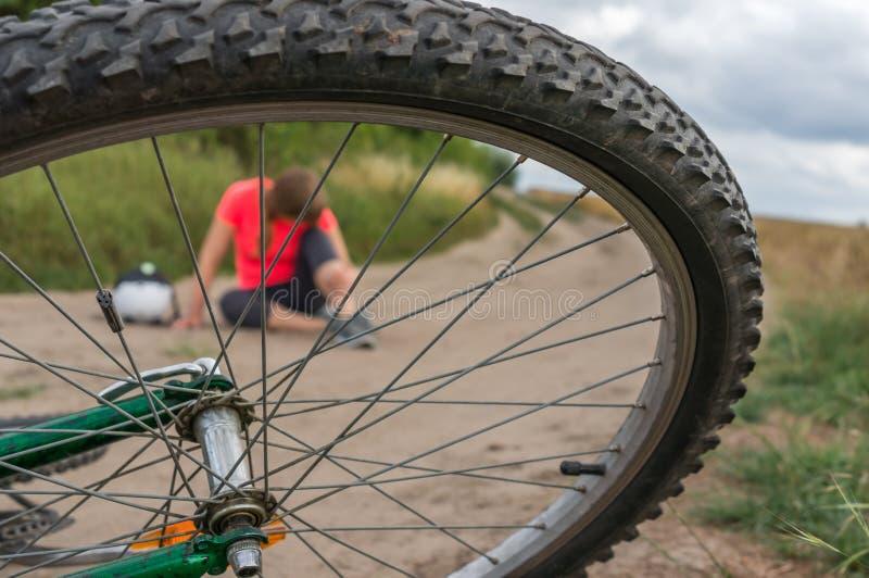 Giovane donna caduta dalla bicicletta della montagna fotografie stock