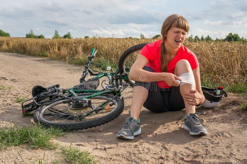 Giovane donna caduta dalla bicicletta della montagna immagini stock