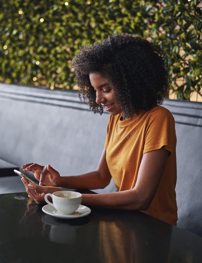 Giovane donna in caffè che pratica il surfing la rete sul telefono cellulare fotografia stock