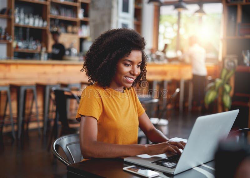 Giovane donna in caffè che scrive sul computer portatile immagine stock libera da diritti