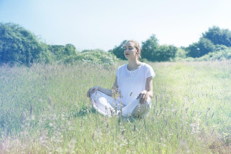 Giovane donna calma di yoga con gli occhi chiusi per consapevolezza concentrata immagine stock