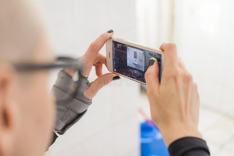 Giovane donna calva ispana che prende le foto con il suo cellulare nella toilette fotografia stock