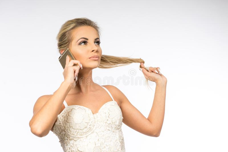 Giovane donna in camicetta bianca La ragazza bionda sta parlando sul telefono cellulare Femmina con il telefono Chiamate della do immagine stock