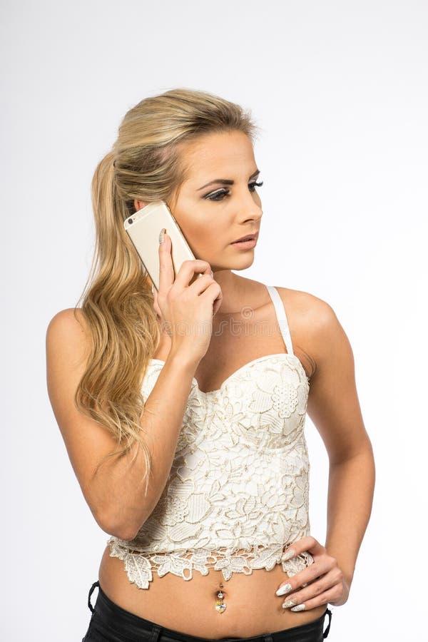 Giovane donna in camicetta bianca La ragazza bionda sta parlando sul telefono cellulare Femmina con il telefono Chiamate della do immagini stock libere da diritti