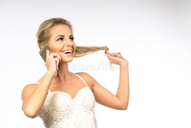 Giovane donna in camicetta bianca La ragazza bionda sta parlando sul telefono cellulare Femmina con il telefono Chiamate della do fotografie stock libere da diritti