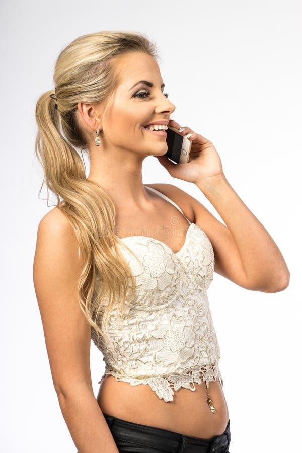 Giovane donna in camicetta bianca La ragazza bionda sta parlando sul telefono cellulare Femmina con il telefono Chiamate della do immagini stock