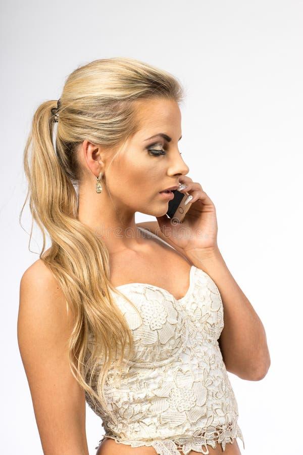 Giovane donna in camicetta bianca La ragazza bionda sta parlando sul telefono cellulare Femmina con il telefono Chiamate della do fotografia stock libera da diritti