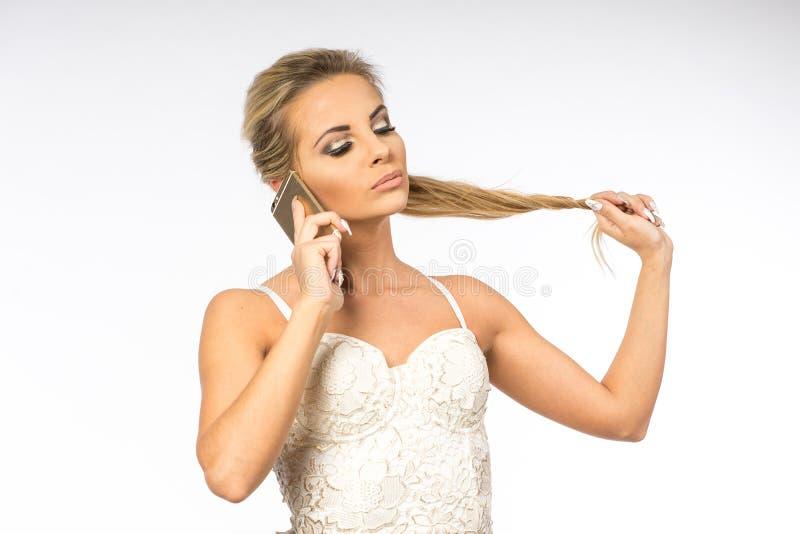 Giovane donna in camicetta bianca La ragazza bionda sta parlando sul telefono cellulare Femmina con il telefono Chiamate della do fotografie stock
