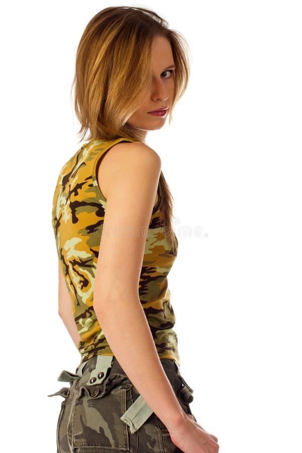 Giovane donna in camuffamento che osserva sopra la spalla fotografia stock libera da diritti