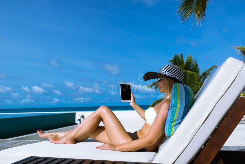Giovane donna in cappello con il pc della compressa alla spiaggia fotografia stock libera da diritti