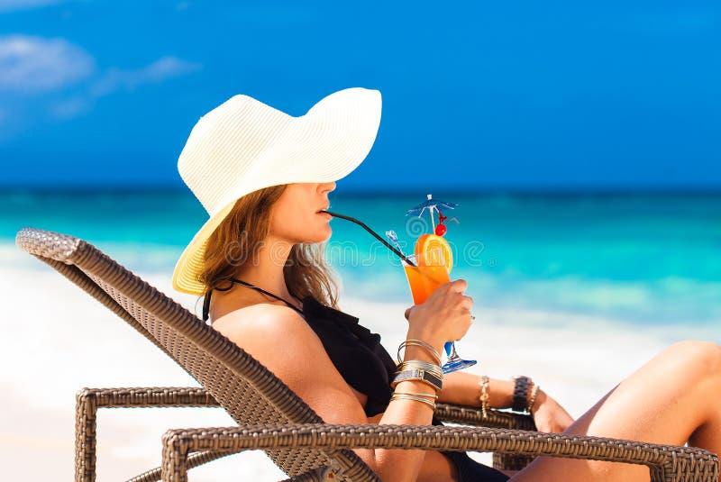 Giovane donna in cappello di paglia che pone alla spiaggia e al enjoyi tropicali immagine stock libera da diritti