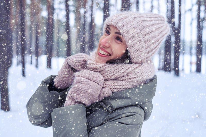 Giovane donna in cappuccio alla moda e sciarpa tricottati caldi che guardano verso l'alto fotografia stock libera da diritti