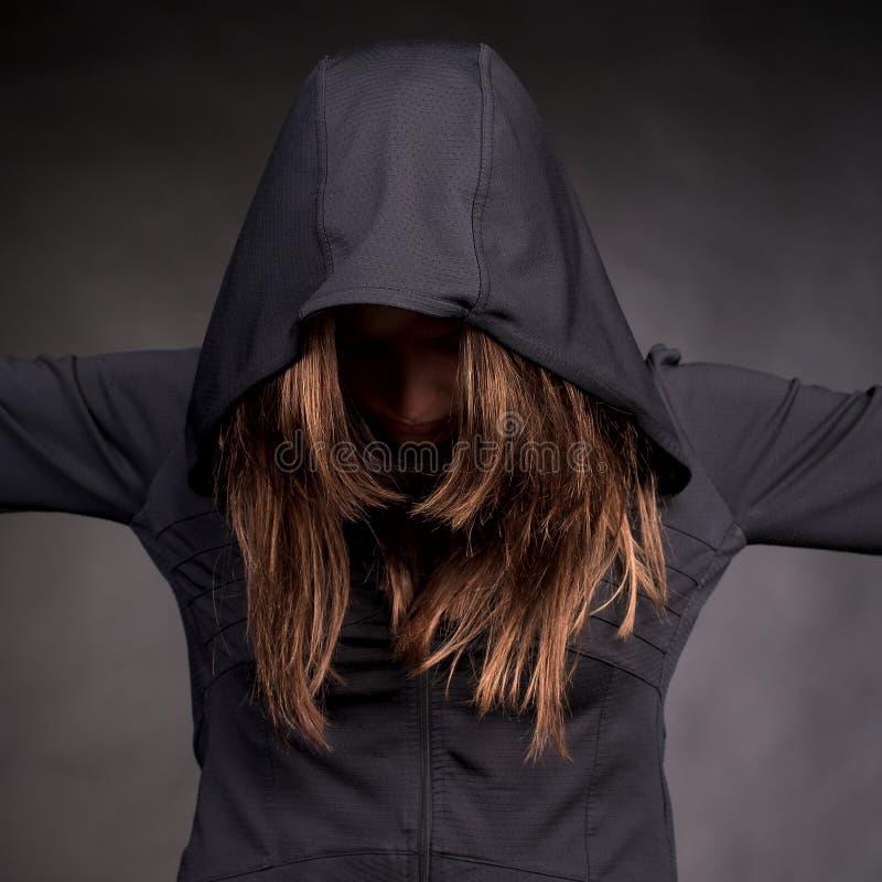 Giovane donna in cappuccio con nascosto fotografia stock