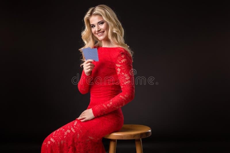 Giovane donna in casinò con le carte sopra fondo nero mazza immagini stock