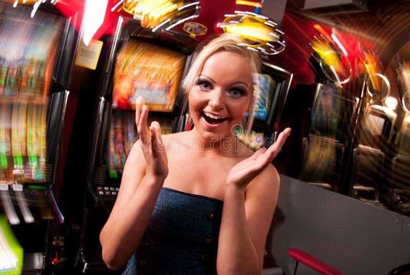Giovane donna in casinò su uno slot machine fotografie stock
