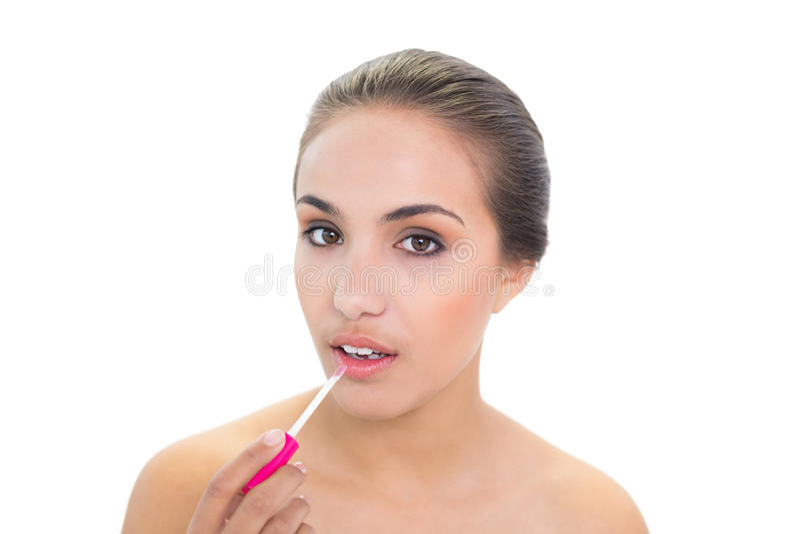 Giovane donna castana adorabile che applica lucentezza del labbro fotografia stock libera da diritti