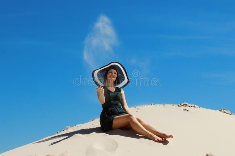 Giovane donna castana adulta che si rilassa su una spiaggia Donna felice che gioca con la sabbia alla spiaggia Sabbia di lancio d fotografia stock