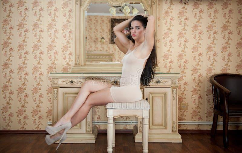 Giovane donna castana affascinante in vestito nudo da short stretto di misura davanti ad uno specchio Ragazza lunga splendida sex fotografia stock libera da diritti