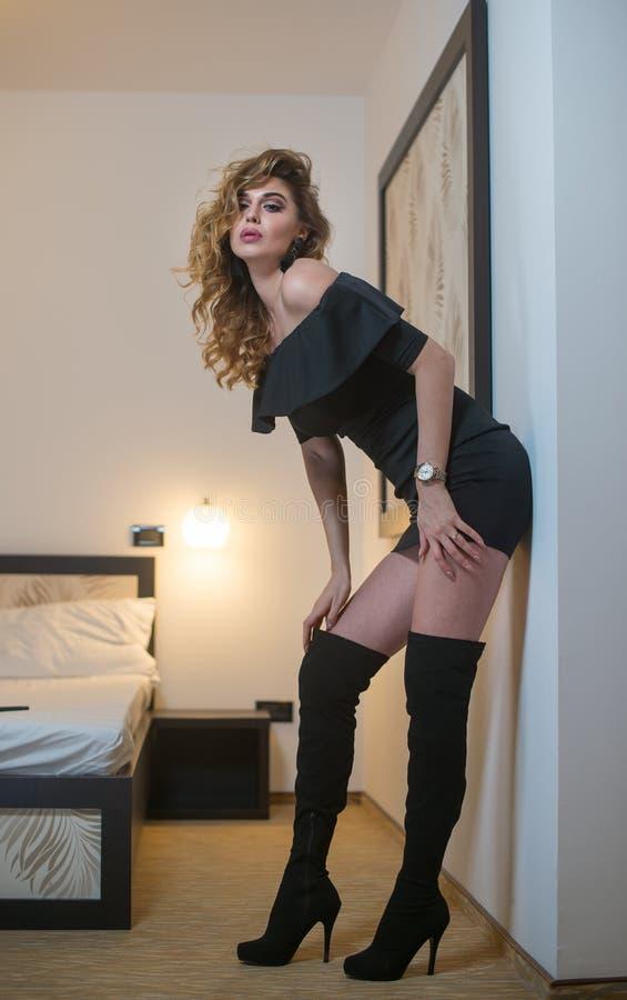 Giovane donna castana affascinante in vestito stretto dal nero di short di misura che pende contro la parete Ragazza splendida se immagine stock