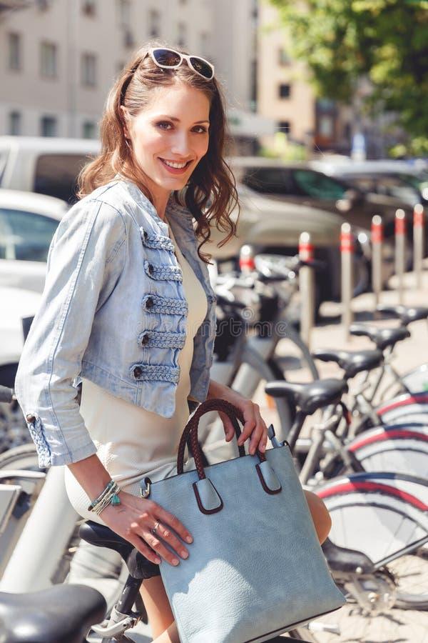 Giovane donna castana alla moda che si siede sulla bicicletta fotografia stock