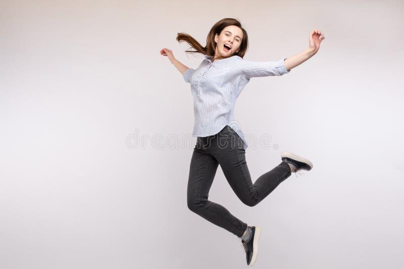 Giovane donna castana allegra nella prospettiva casuale che salta in metà di aria in studio fotografie stock