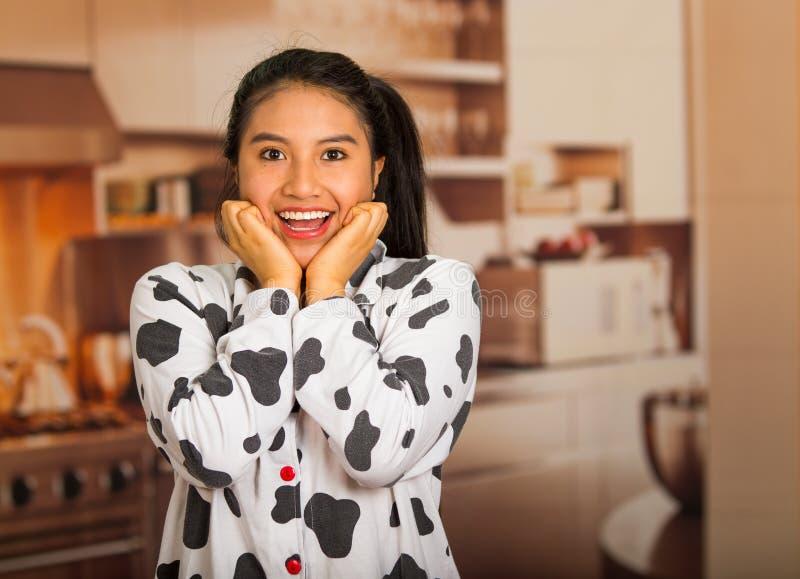 Giovane donna castana che posa nei pigiami e che affronta macchina fotografica mentre toccando fronte facendo uso delle mani, sem immagini stock