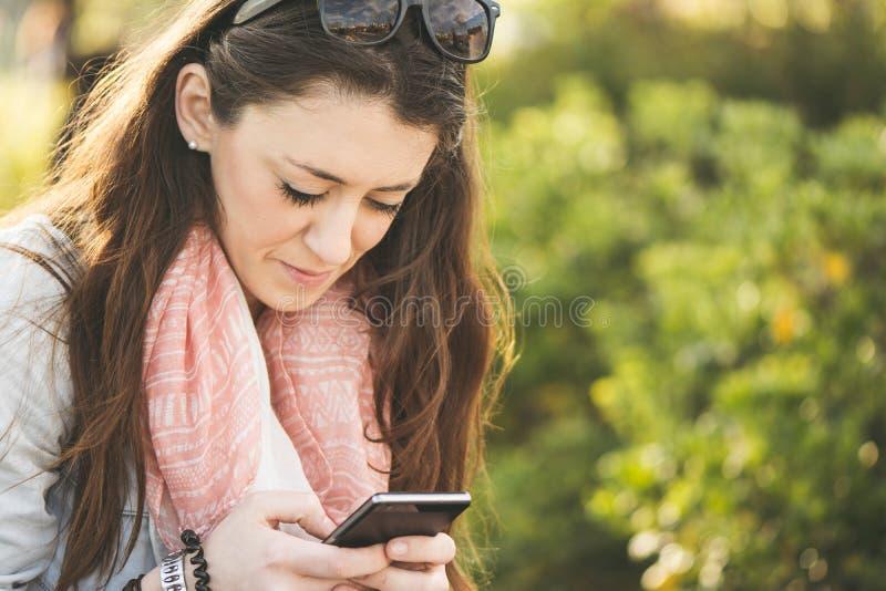 Giovane donna castana che scrive sopra il telefono fotografia stock libera da diritti