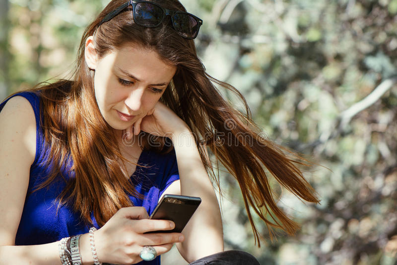 Giovane donna castana che scrive sopra il telefono immagini stock