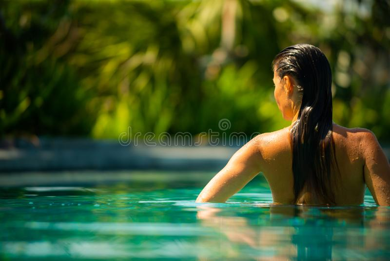 Giovane donna castana che si rilassa dal lato dello stagno di infinito immagini stock libere da diritti