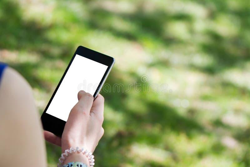 Giovane donna castana con il cellulare in vostre mani fotografia stock
