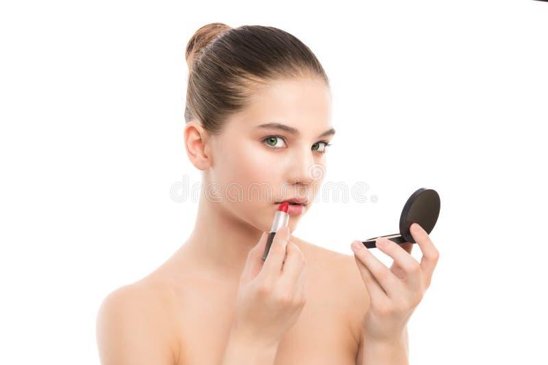 Giovane donna castana con il fronte pulito perfetto che applica rossetto facendo uso dello specchio Su un bianco immagini stock