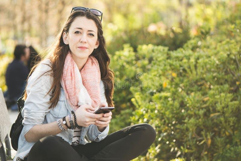 Giovane donna castana con il telefono a disposizione, sedendosi nel parco immagini stock libere da diritti