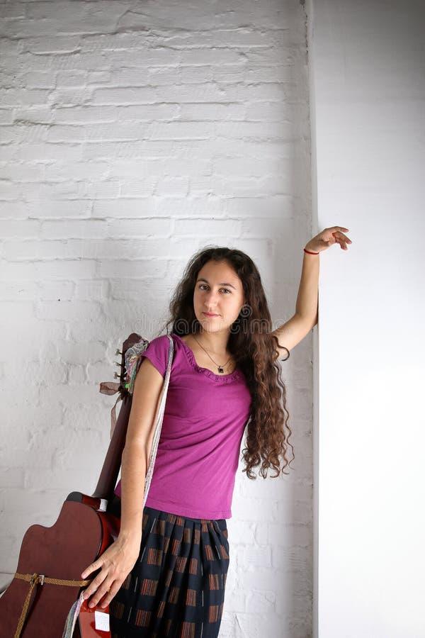 Giovane donna castana con la chitarra acustica in gonna lunga Priorità bassa del muro di mattoni immagini stock libere da diritti