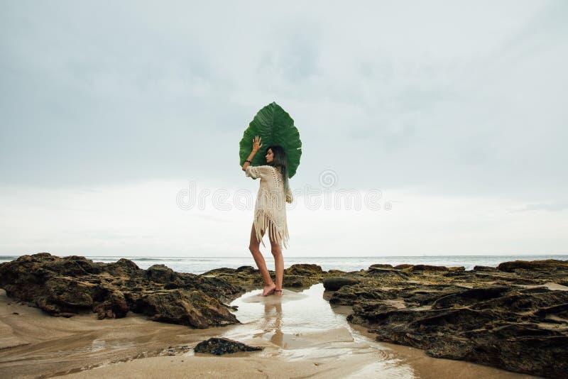 Giovane donna castana del ritratto con una foglia di palma che sta sul mare della costa del fondo fotografie stock