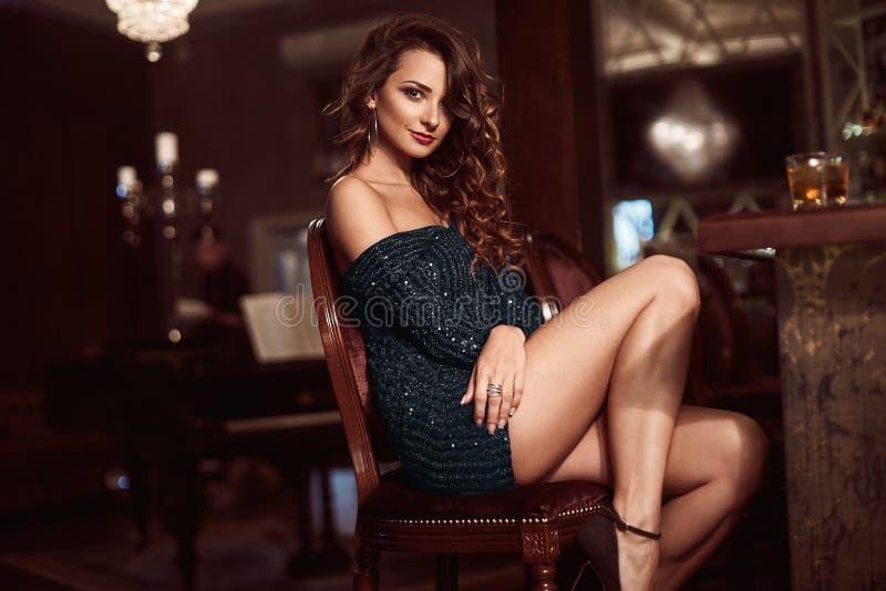 Giovane donna castana di bellezza che si siede alla barra fotografia stock