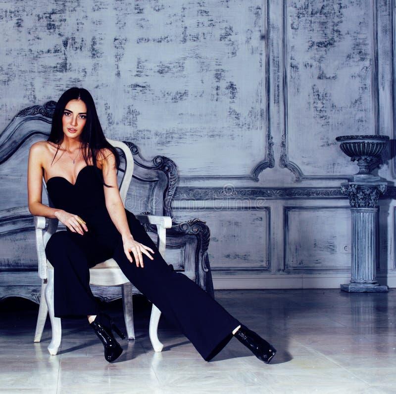 Giovane donna castana di bellezza nell'interno domestico di lusso, camera da letto leggiadramente nei gradi di grey fotografia stock
