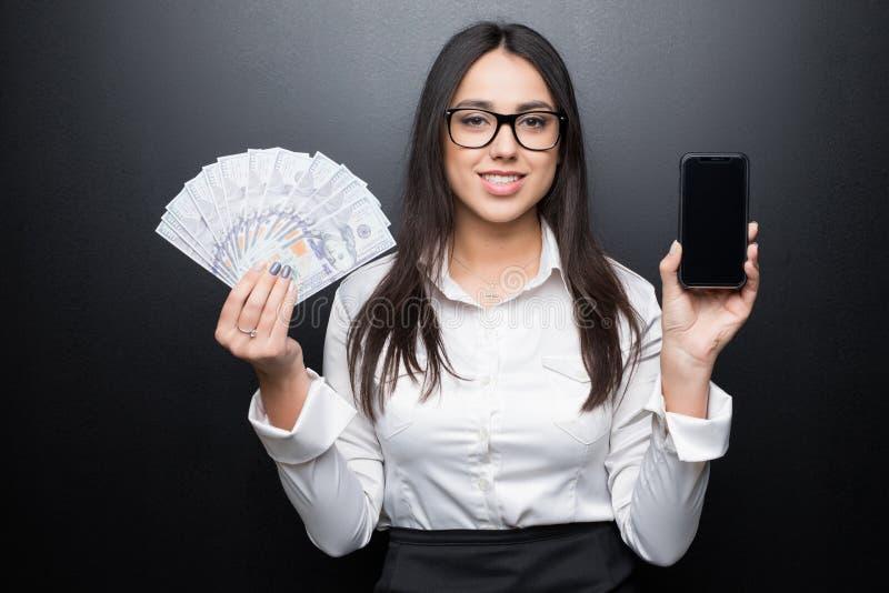 Giovane donna castana felice in camicia bianca che mostra smartphone con lo schermo in bianco ed il denaro contante in mani su ba fotografie stock libere da diritti