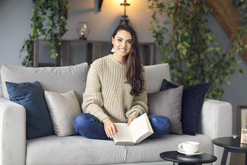 Giovane donna castana felice con il maglione d'uso del libro immagini stock
