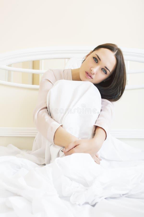 Giovane donna castana graziosa che pone a letto da solo attesa sexy, concetto della gente di stile di vita immagine stock