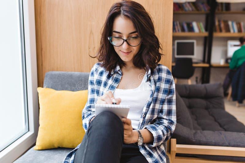 Giovane donna castana intelligente in vetri neri che si siedono sulla finestra a casa, scrivendo un rapporto in taccuino comodo fotografia stock libera da diritti