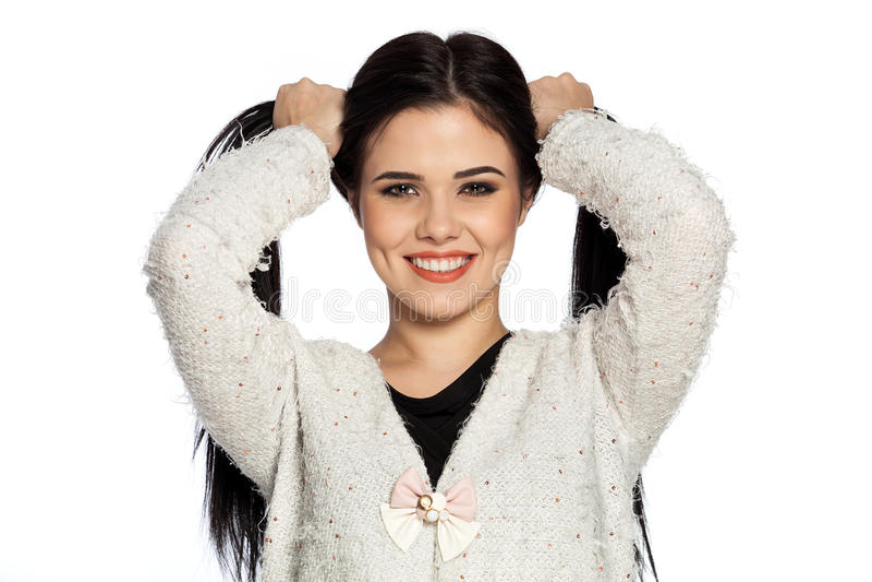 Giovane donna castana sorridente che tiene due code di cavallo fotografie stock libere da diritti