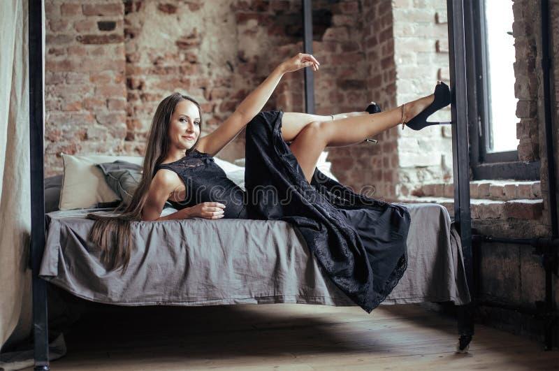 Download Giovane Donna Castana In Sottotetto Che Mette Su Sorridere Del Letto Fotografia Stock - Immagine di palazzo, bellezza: 56892594