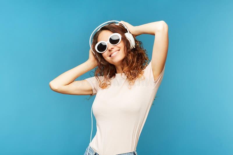 Giovane donna castana spensierata in jeans e maglietta che ascolta la musica fotografie stock