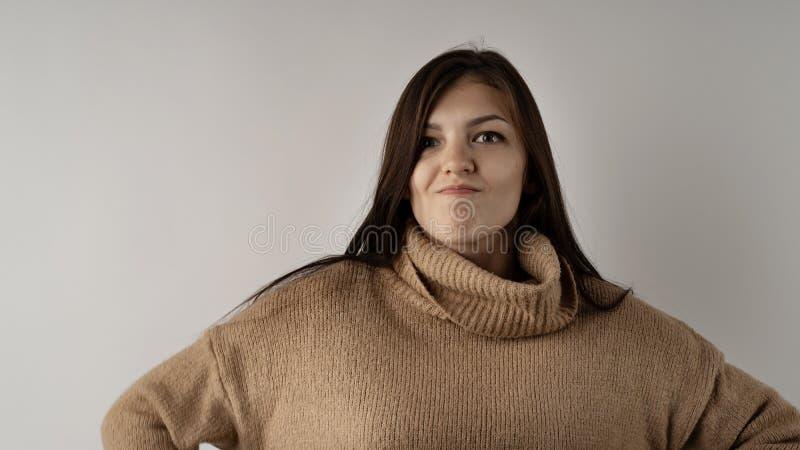 Giovane donna castana splendida in maglione tricottato caldo su fondo grigio chiaro fotografie stock libere da diritti